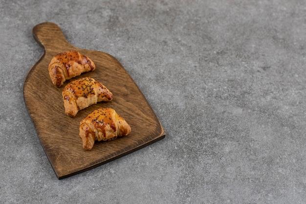 회색 표면 위의 나무 커팅 보드에 있는 맛있는 홈메이드 쿠키 클로즈업