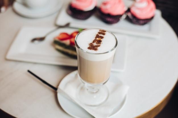 초점 없는 배경에 컵케이크와 케이크가 있는 테이블에 유리로 만든 맛있는 뜨거운 라떼 커피 클로즈업.