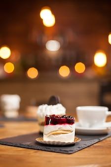 コーヒーショップの木製のテーブルの上に果物を載せたおいしいミニケーキのクローズアップ。おいしい一杯のコーヒー。上にビスケットが入ったケーキ。
