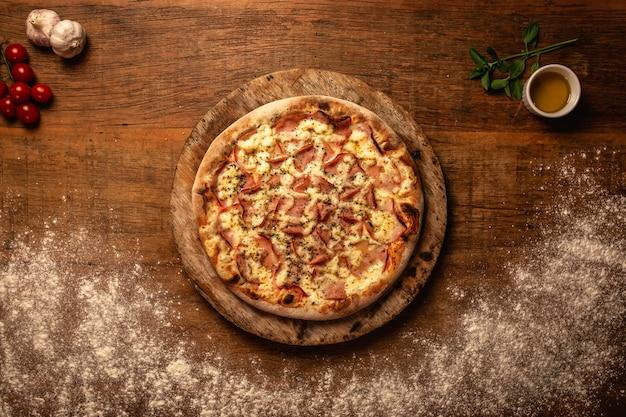 木製のまな板でおいしいピザのクローズアップ