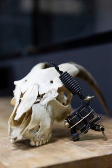 タトゥースタジオでヤギの頭蓋骨に休んでいるタトゥー銃のクローズアップ。テキスト用のスペース。