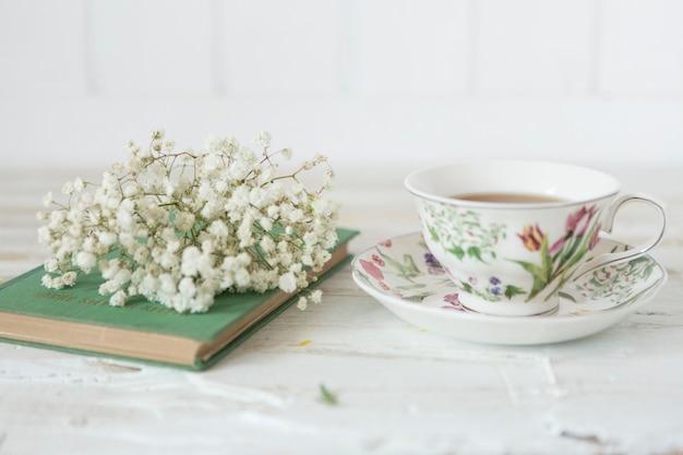Крупным планом чашку чая, цветы и книги