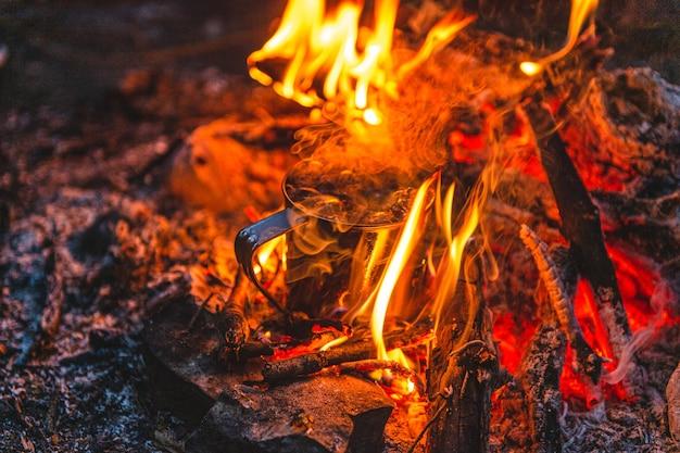 금속 머그잔에 차 가까이 모닥불에 가열