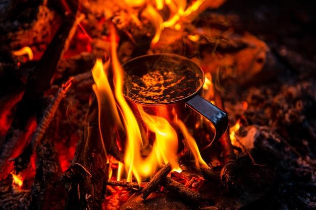 금속 머그잔에 차 가까이 모닥불에 가열 프리미엄 사진
