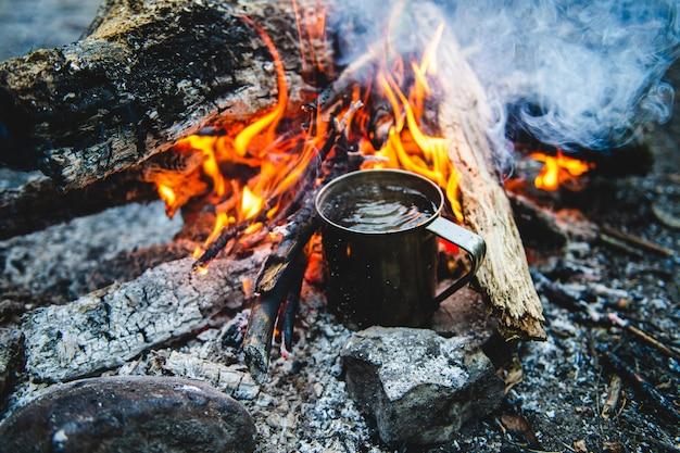 Крупным планом чай в металлической кружке нагревается в костре