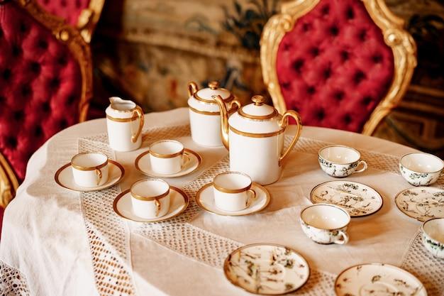 Крупный план чайных сервизов на белой кружевной скатерти с плюшевыми красными стульями
