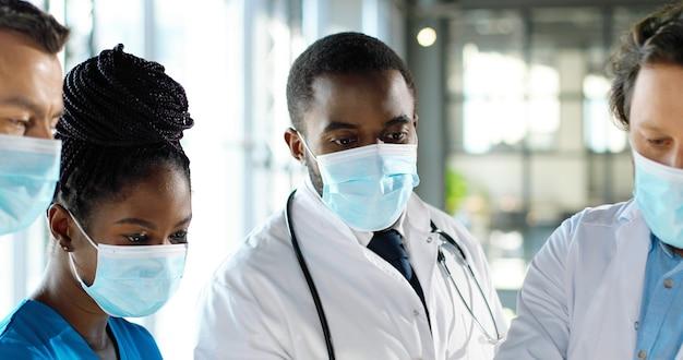 Закройте команду коллег врачей смешанных рас, обсуждая работу в клинике. группа многоэтнических медиков, мужчин и женщин разговаривают и обсуждают. консультации врачей. совет в больнице