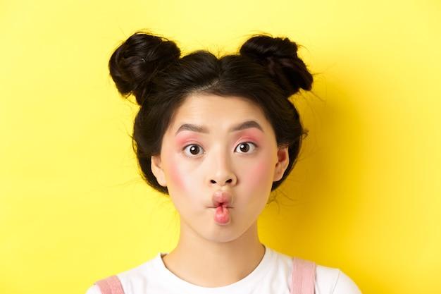 사춘기 한국 소녀 주름 입술의 클로즈업과 매력적인 메이크업과 세련된 헤어 스타일, 노란색으로 서 카메라에 재미를 찾고.