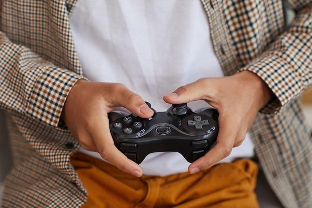 自宅でビデオゲームをプレイしながらゲームパッドを保持している10代のアフリカ系アメリカ人の少年のクローズアップ、コピースペース