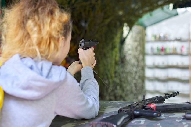 射撃場でトレーニングピストルを撃っている10代の少女のクローズアップ