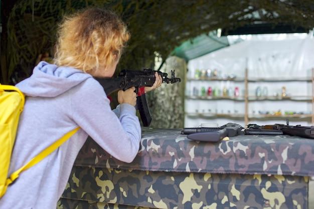 射撃場でトレーニングライフルを撃っている10代の少女のクローズアップ