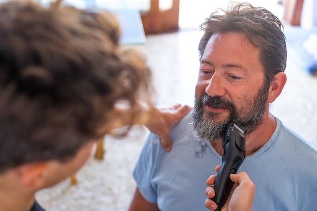 Крупным планом - подросток, стригущий и чистящий бороду своего отца на карантине, чтобы повеселиться и повеселиться вместе дома - два счастливых человека в помещении играют в парикмахерской