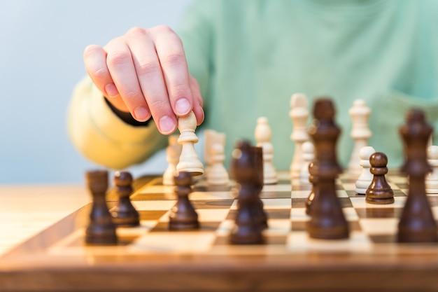 チェスをしながら木製のポーンの図を保持しているティーンエイジャーの手のクローズアップ