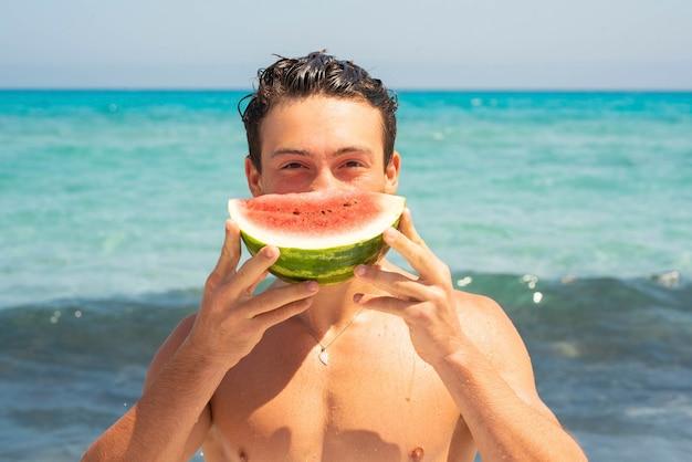 顔の前にスイカを持っているティーンエイジャーのクローズアップ。半分のスイカの果実を保持し、海の水面の前でカメラを見ている上半身裸の10代の少年の肖像画
