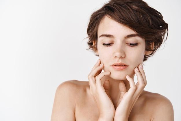 Крупный план нежной кавказской женщины с короткой стрижкой и обнаженными плечами, касающейся гладкой и ухоженной кожи. естественная девушка без макияжа, стоящая над белой стеной