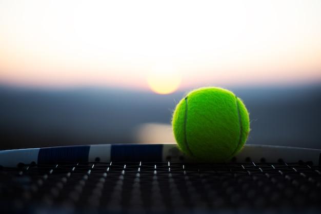 석양 라켓의 그물에 테니스 공의 클로즈업.