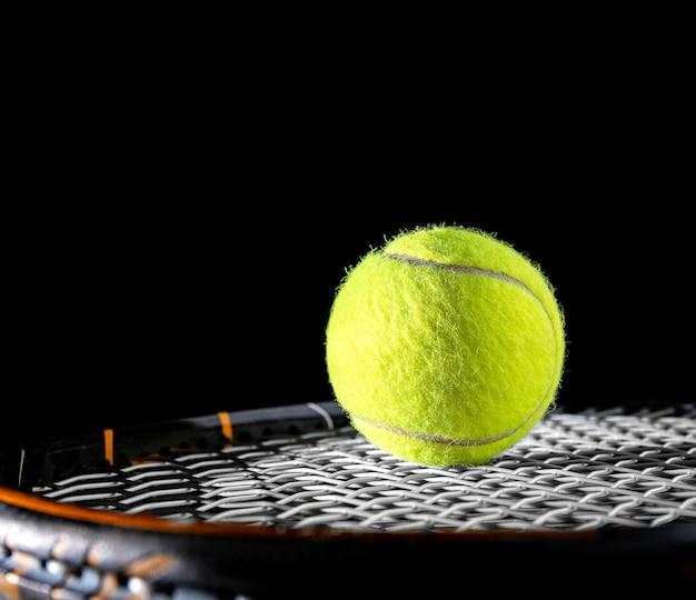 運動や趣味のためのテニスラケットのストリングまたはネット上のテニスボールのクローズアップ