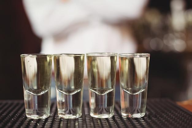 バーのカウンターにショットグラスのテキーラのクローズアップ