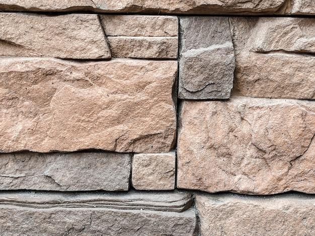 건물 장식에서 회색과 베이지색 톤의 마주보는 벽돌 질감의 클로즈업. 건설 및 건축 개념입니다.