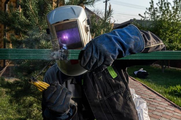溶接工のクローズアップは、村の建設現場でフェンスを溶接します