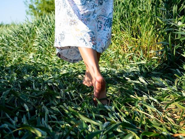 夕方に芝生の上を歩いているドレスを着た女の子の素足のクローズアップ