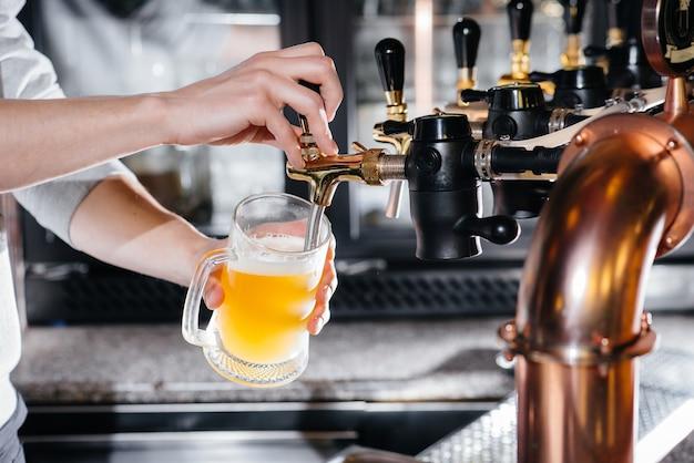 가벼운 맥주 한 잔을 채우는 바텐더의 클로즈업. 펍의 바 카운터.