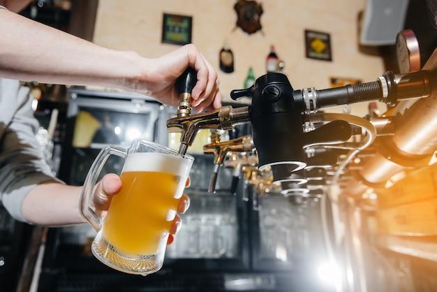 Крупный план бармена, наполняющего кружку светлого пива. барная стойка в пабе.