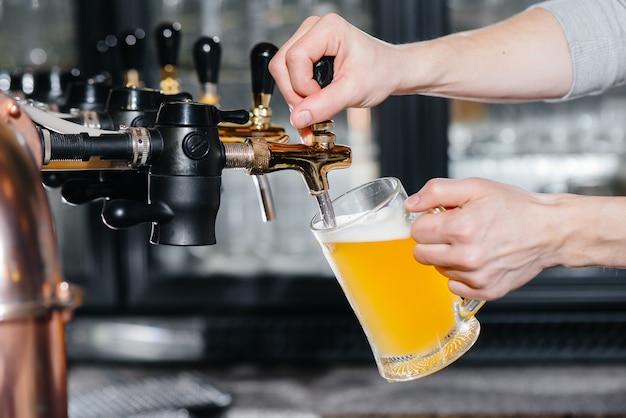 軽いビールのマグカップを満たすバーテンダーのクローズアップ。パブのバーカウンター。