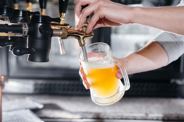 Крупный план бармена, наполняющего кружку светлого пива