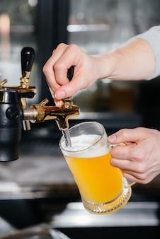 라이트 맥주 머그잔을 채우는 바텐더의 클로즈업