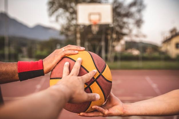 세 선수의 손에 농구의 클로즈업. 농구 경기 시작