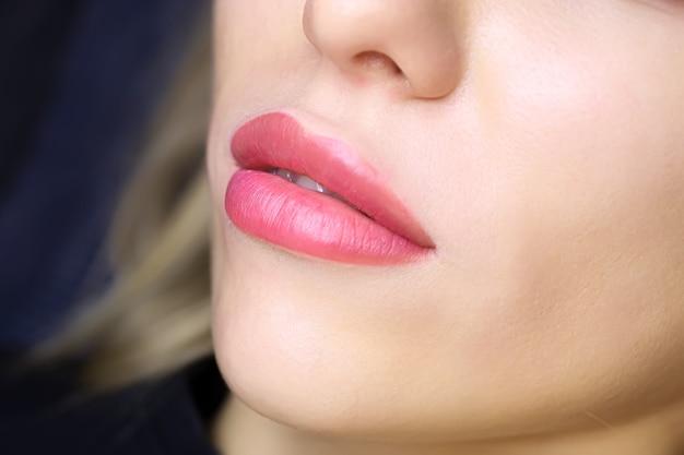 唇の入れ墨を持つ若いモデルの美しい唇のクローズアップ