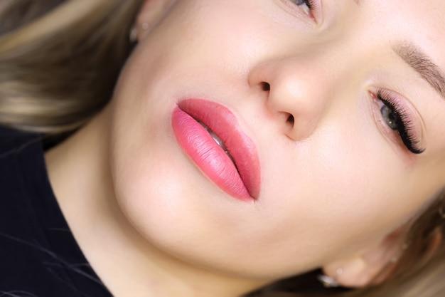 Крупный план красивых губ молодой модели с татуировкой губ