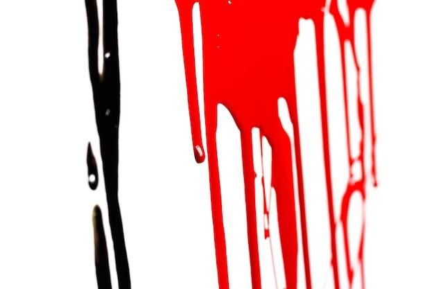 白の背景に分離された黒と赤の流れるペイントのクローズアップ
