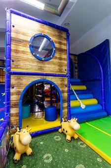 놀이터에 있는 파란색과 노란색의 크고 부풀릴 수 있는 성 미로를 닫습니다