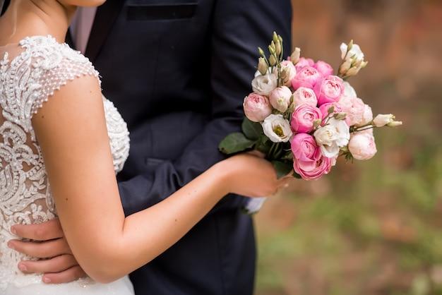 彼女の手で花嫁の花束のクローズアップ。繊細な白、ピンク、クリーム色のバラ