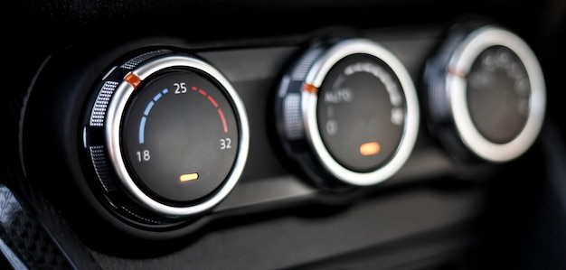 자동차 에어컨 제어 버튼의 클로즈업입니다. 3개의 자동 에어컨 조절 손잡이, 온도 조절 손잡이가 있습니다.