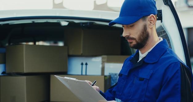 カートン小包でいっぱいのバンでドキュメントを書いている白人の魅力的な男性労働者のクローズアップ。外側。