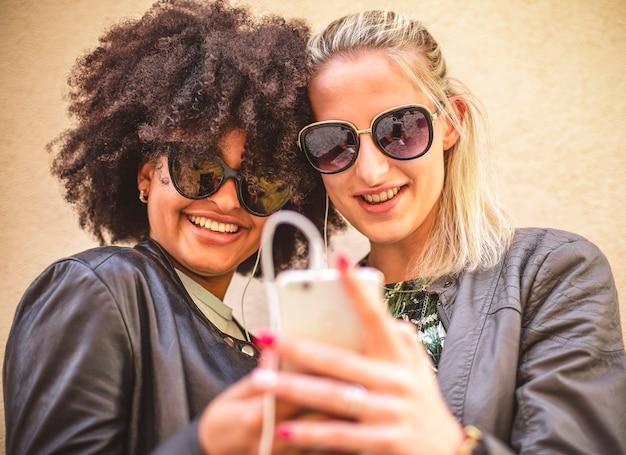 Крупный план сотового телефона в руке двух девушек.