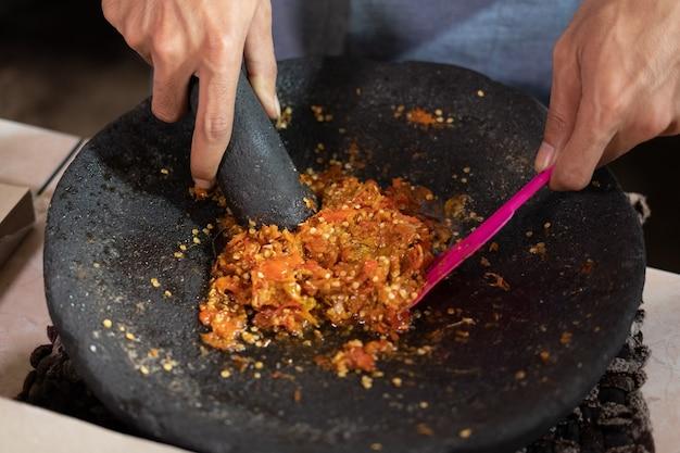調理用乳鉢でスパイスをすりつぶしながら、料理人の手のクローズアップ