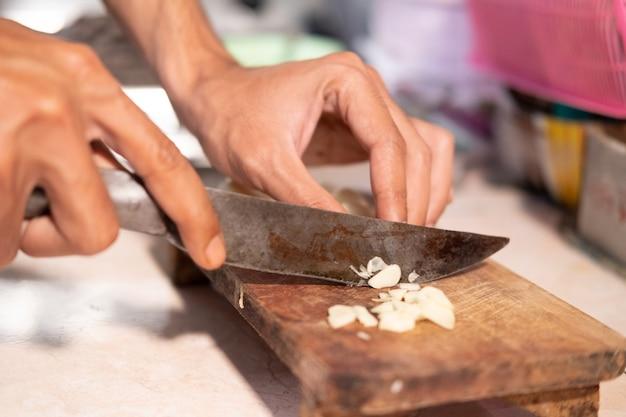 ナイフと木製のまな板でニンニクをスライスしながら、料理人の手のクローズアップ