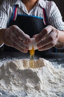 계란을 밀가루로 부수는 요리사의 손을 닫습니다.