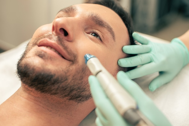 Крупным планом косметолога, проводящего процедуру питания кожи на лице бородатого мужчины