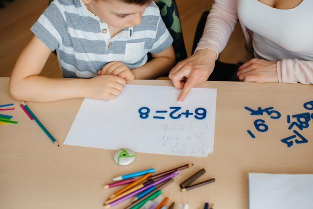 私が宿題をするデスクトップのクローズアップと母親と一緒に男子生徒。調査