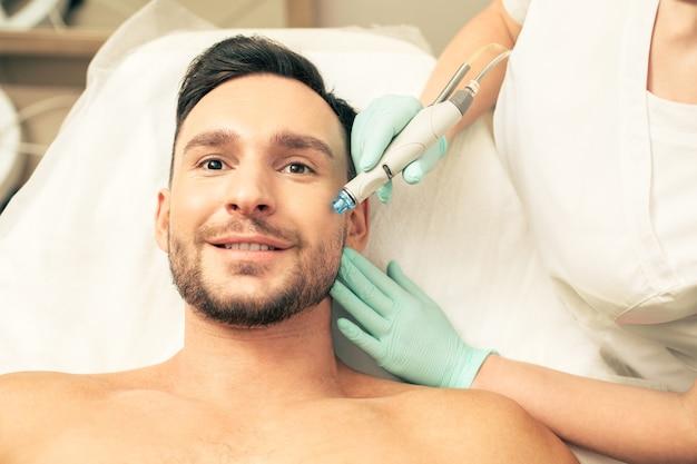 Крупным планом эмоциональный молодой человек выглядит впечатленным и улыбается во время процедуры по питанию кожи с помощью современного инструмента.