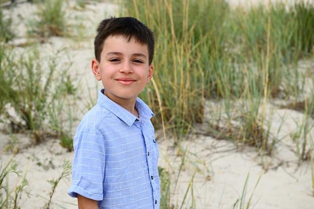 Крупный план лица милого улыбающегося подростка, стоящего на фоне степных зарослей и песчаной почвы. красивый ребенок мило улыбается, глядя в камеру. выстрел в голову очаровательного ребенка