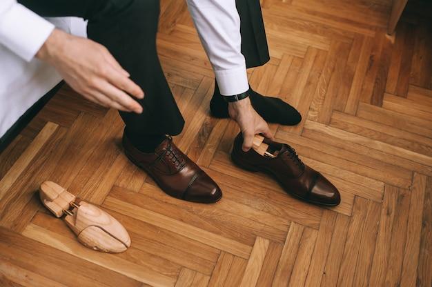 新しいスタイリッシュな靴を履いている新郎やビジネスマンの足のクローズアップ。男性の手は靴から木製のインサートを取り出します。人、ビジネス、ファッション、靴のコンセプト。
