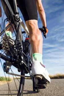 Крупный план ноги молодого человека, едущего на велосипеде по дороге.