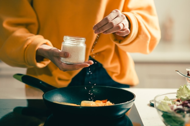 Крупным планом сковорода и женщина в желтом свитере, добавляющая кокосовую стружку к еде