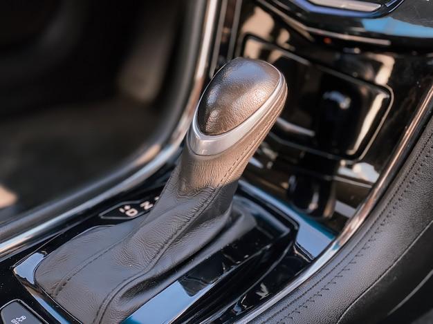 Крупный план рычага переключения передач внутри автомобиля. фото салона автомобиля в черном цвете.